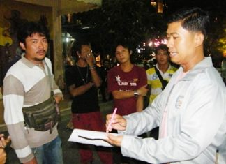 Krit Suwanpiyawong (left) is taken into custody by Maj. Wasu Sangsuksai (right), chief of Pattaya City Hall's regulatory enforcement department.