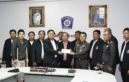 """Top police officials award 30,000 baht each to two Banglamung police officers in compensation for injuries sustained in a late night shooting and the subsequent arrest of suspects Surachat """"Tam Nakrob"""" Kaewchingduang and Aris """"Kai"""" Wangweng."""