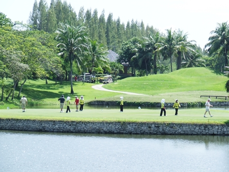 Golfers take on the challenging island green signature hole.