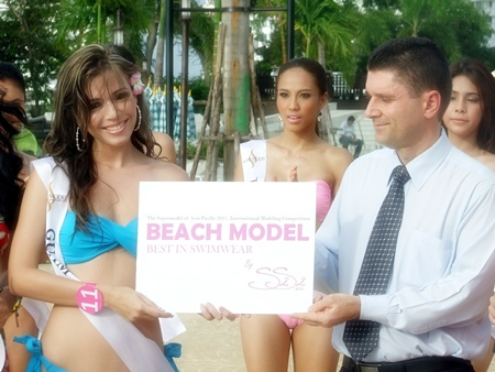 Kate Kikuchi, from Guam (left) receives first prize in the swimsuit category from Joachin Grill, General Manager of Royal Cliff Hotels Group.