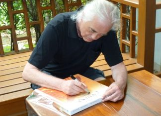 Jimmy Page signs an auction item.