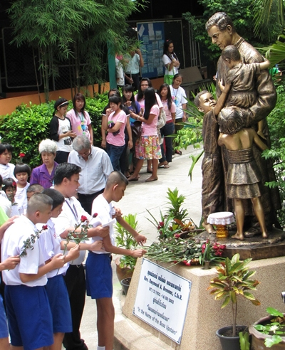 The blind students lay single red roses on Father Ray's statue.