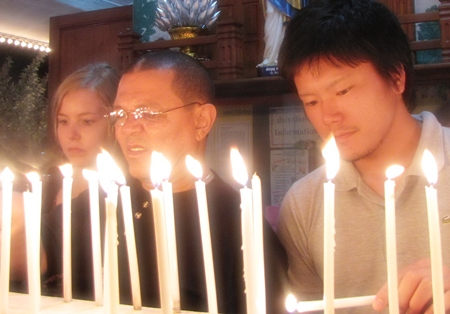 Volunteers from Germany, South Africa and Japan light a candle at the Memorial Mass.