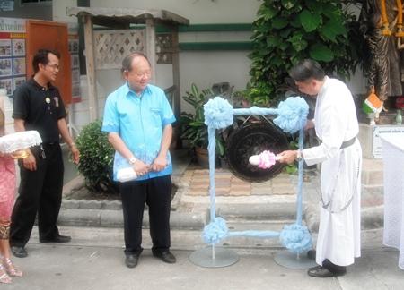 Fr. Pattarapong Srivorakul strikes the gong to start the proceedings as Nongprue Mayor Mai Chaiyanit looks on.