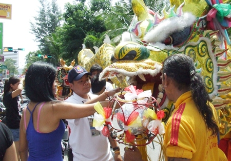 Feeding money to the dragon for good luck. (Photo by Phasakorn Channgam)