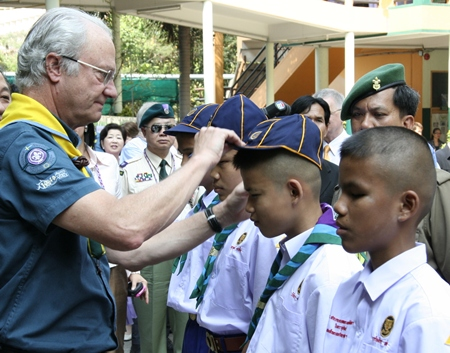King Carl XVI Gustav of Sweden presents Scout caps to the blind students.