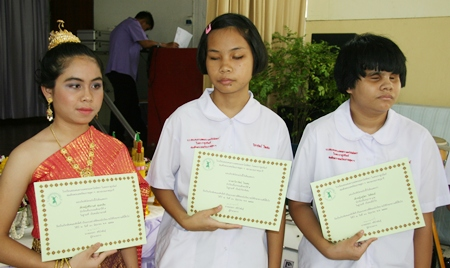 Three blind students with their 'Awards for Excellence'.