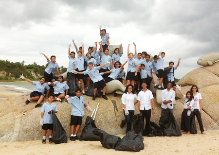 Year 7 students celebrate after cleaning the beach.