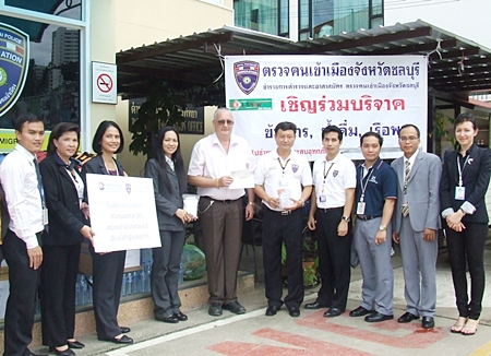 Neera Sirisamphan (3rd left) and Steve Graham (5th left) present their respective donations to Pol. Col. Choosak Panusamporn commander of Chonburi Immigration for their flood relief efforts.