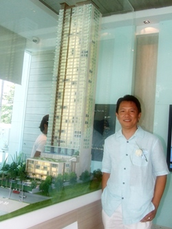 Vichapol Srisuriyachai, managing director of Bellagio Development Co. Ltd., stands next to a model of the new Cetus Condominium during the launch of the project's showroom, Saturday, October 1.