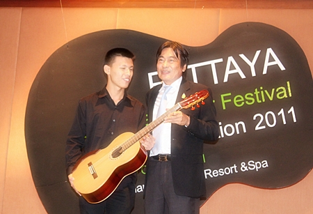 Winner of the 2011 Guitar Festival competition, Chinnawat Themkumkwun (left) accepts his prize guitar from Deputy Mayor of Pattaya, Ronnakit Ekasing.