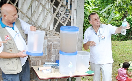 Rotarians Jan Abbink and President Carl Dyson demonstrate the simplicity of the drip filters and the purity of the filtered water.