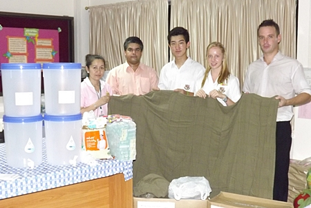 Tony Malhotra (2nd left) and Andrew Emerey (right) together with students from St Andrews brought life-saving water filters and Swiss International Air Lines blankets for the children.