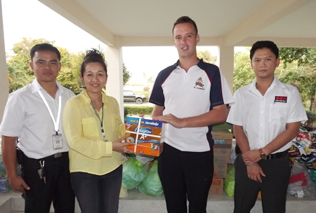 Andy Emery (2nd right) and two members of the SECURITAS staff donate necessities to Pinya Jumroonsan (2nd left) from the Rangsit Babies Home.