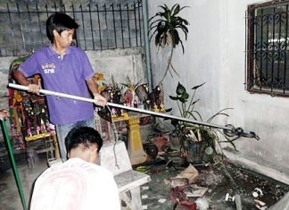 Sawang Boriboon animal experts remove the cobra from the flower garland shop.