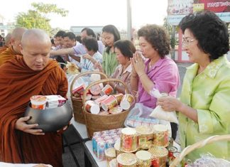 Good hearted Banglamung citizens fill monks' bowls with much needed supplies to give to flood victims currently living in local shelters.