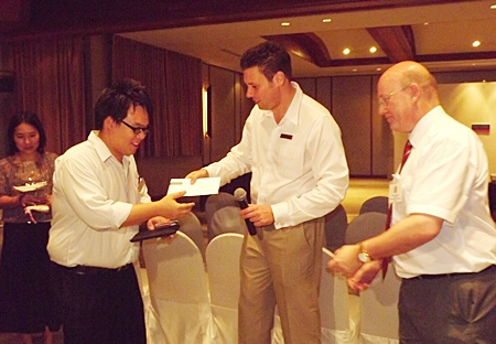 Clinton Lovell GM of the Aisawan Pullman presents the winner with his lucky draw prize.