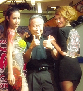 """Royal Garden Managing Director Supadit Maneeratjarusri (center) poses with Athma """"Bowie"""" Chiewanitpan (right) and a sexy model, the latter two showing off the body paint artwork they were given at the festival."""