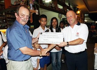 Alec Hoare (right) presents a cheque for 500,000 baht on behalf of the family of the late Benny O'Connor to Stephen Beard (left), to be donated to the Baan Jing Jai children's home.