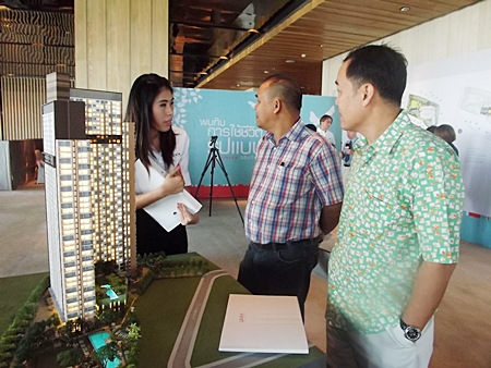 Interested buyers and a Raimon Land sales representative stand next to a scale model of the Unixx project at an open day held at the Hilton Hotel Pattaya on Saturday, Dec. 10.