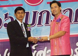 Kasem Chiewjew (left), principal of Pattaya School No. 9, receives an award for outstanding principal of the year from Mayor Itthiphol Kunplome.