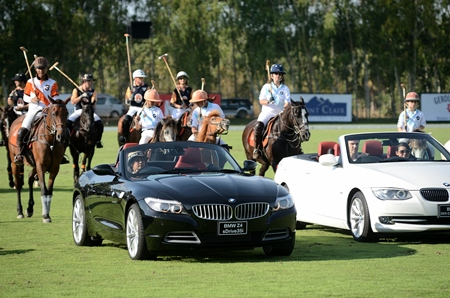 The pre-final parade is led from behind the wheel of a black BMW Z4 by Nunthinee Tanner, co-owner of the Thai Polo & Equestrian Club.