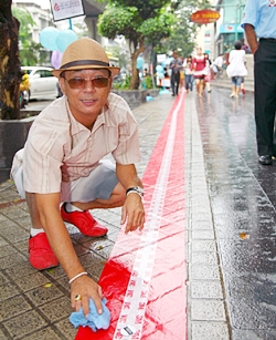 The red carpet along Silom Road is dotted with stickers, each representing a donated coin.
