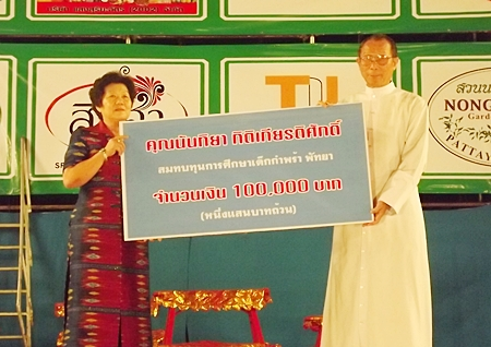 Feiyan troupe organizer Nanthiya Kittikiettisak presents orphanage Director Rev. Veera Phangrak with a donation of 100,000 baht.