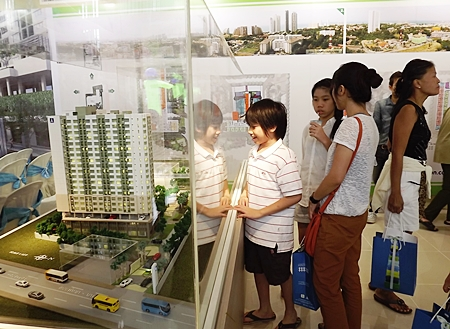Visitors look at a scale model of the development.