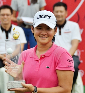 Yani Tseng shows off the trophy on the 18th green following the presentation ceremony.