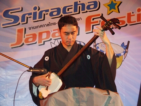 A musician plays the traditional Shamisen (Japanese 3-stringed banjo).