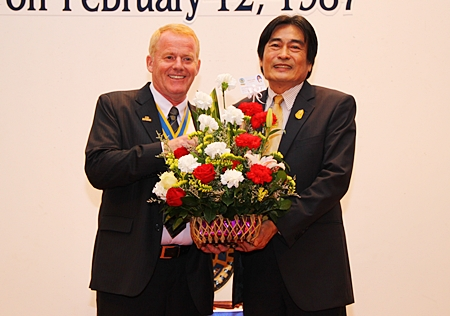 Deputy Mayor Ronakit Ekasingh presents a bouquet to President Gudmund Eiksund.