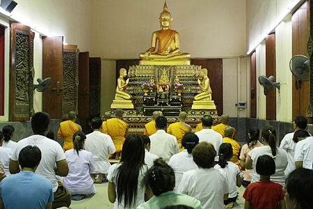 Faithful Buddhists pray and listen to monks chant on Buddhist All Saints Day at Wat Nong Prue.