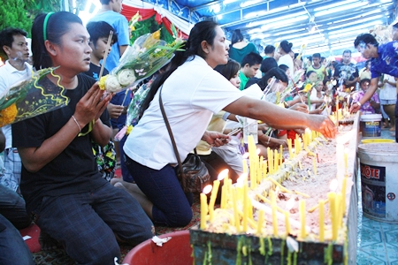 Buddhists light candle and joss sticks at Wat Satawat.