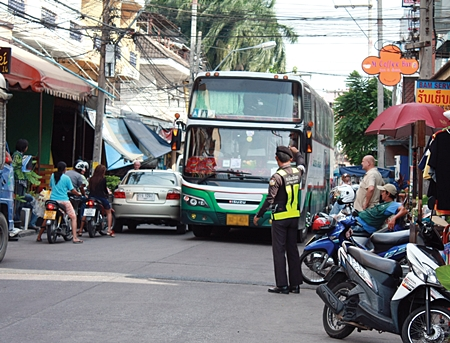 Some bus drivers still haven't learned the size of their buses, and often attempt to drive them places where they don't belong.  Here, municipal officer Kietinarong Panpra helps guide a large bus down a narrow soi.  For more on what municipal officers' duties are in helping the city.