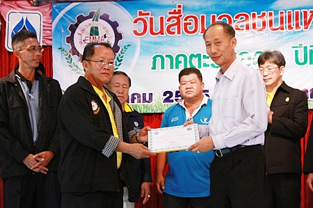 Padungsak Tantraworasilp, president of the Eastern Mass Media Association of Thailand, receives his prestigious award from Chonburi Governor Khomsan Ekachai.