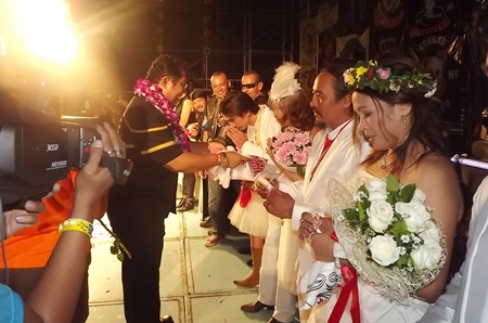 "Sonthaya Kunplome, former Minister of Sports and Tourism, presents Burapha flags to ""just married"" couples."