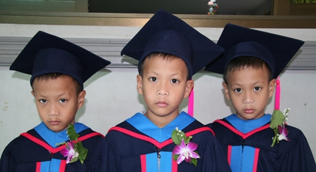 Three brothers, identical triplets, don't look too happy in their graduating gowns.
