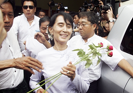 Myanmar pro-democracy leader Aung San Suu Kyi receives flowers from supporters as she leaves the headquarters of her National League for Democracy party in Yangon, Myanmar Monday, April 2. Suu Kyi claimed victory Monday in Myanmar's historic by-election, saying she hoped it will mark the beginning of a new era for the long-repressed country. (AP Photo/Khin Maung Win)