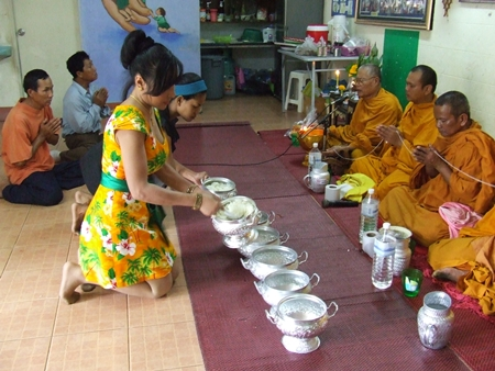 Sukanya Seaton, president of Seaton Foundation Pattaya, serves rice to monks.