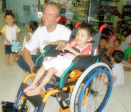 Woody visits with Fah Sai, who is in wheelchair donated by Jesters, at the Hand to Hand Foundation.