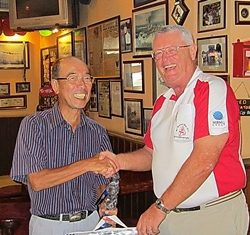 Mashi Kaneta (left) receives the 'golfer of the month' award from Dick Warberg.