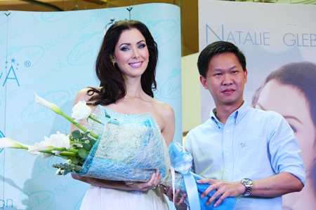 Miss Universe 2005 Natalie Glebova receives a bouquet of flowers from Somporn Naksuetrong, general manager of Ripley's Believe it or Not! Museum Pattaya.