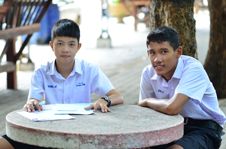 Bodhisamphan students Sarayut Maneechuen (left) and Nathwut Nuanphulb (right) do some of their homework outside in the fresh air.