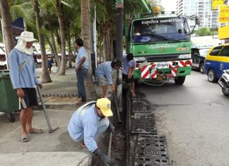 Sanitation Engineers clean dirt, garbage and sand out of the drainage pipes on Beach Road in Central Pattaya.