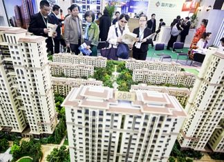 People look at models of new residential developments for sale at a real estate fair in Beijing, China. (EPA/Diego Azubel)