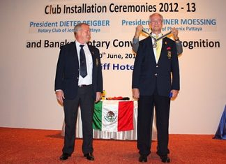 Newly elected president Dieter Reigber (right) receives his medal from the district governor (not shown), while his predecessor Gudmund Eikson looks on.