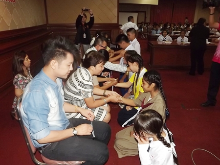 Student contestants have their wrists tied in sai sin for good luck and protection.