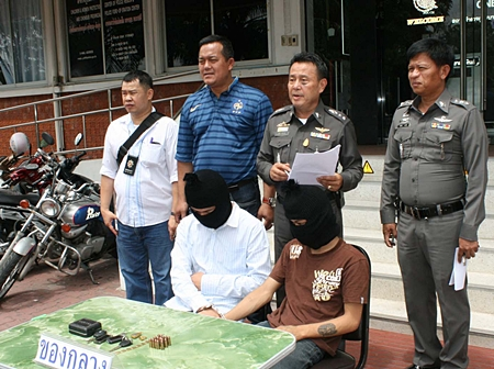 Pol. Col. Somnuk Changate (2nd right) brings out the 2 underage boys, part of a gang that robbed a policeman's condo.