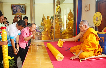 Nongprue Mayor Mai Chaiyanit (center right), and Wat Suthawat School Principal Somchok Yindeesuk (left) donate lent candles to the abbot of Wat Suthawat.